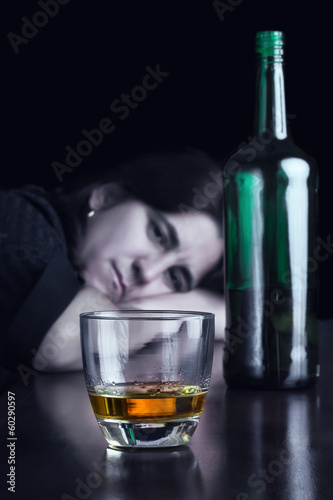 Blue toned dark image of a sad drunk woman
