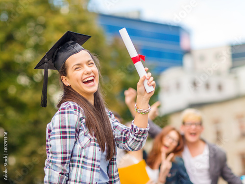 smiling teenage girl in corner-cap with diploma