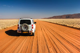 Car on straight lonely sand pad, Namibia - 60291911
