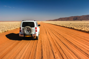 Car on straight lonely sand pad, Namibia