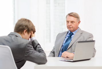 older man and young man having argument in office