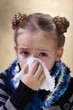 Little girl with the flu blowing her nose