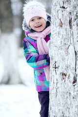 cheerful girl child in the park in winter