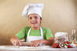 Baker chef boy stretching the dough