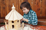Little boy making the last finishing touches on a bird house