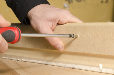 Hands using a screwdriver on wood