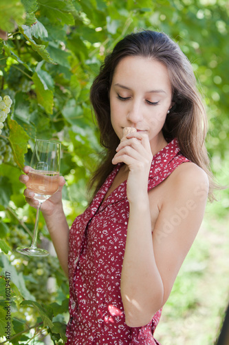 Young woman tasting wine and smell corck