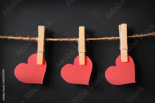 three hearts hanging on blackboard