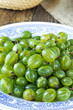 Green gooseberries on white plate