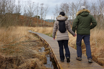 couple holding hands walking along boardwalk on wetland