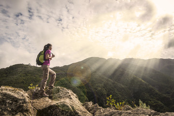 woman hiker with backpack standing on top of a mountain and enjo