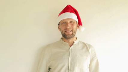 Happy man in santa hat stand by the wall
