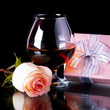 Glass with alcohol and rose and gift box