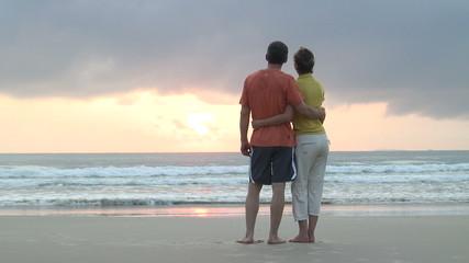 Paar genießt Sonnenaufgang am Meer