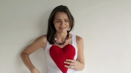 Angry, unhappy woman with heart shape pillow
