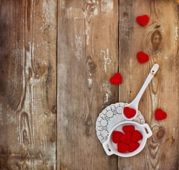 Cup, spoon and hearts on a wooden background.