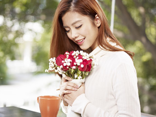 young woman smelling the fragrance of flowers