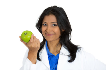 Happy smiling female doctor holding a green apple