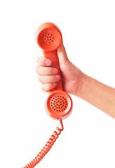 Hand holding an old orange telephone isolated on white