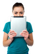 Shy pretty model hiding face with tablet pc