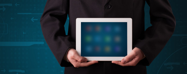 Businessman holding a white modern tablet with blurry apps