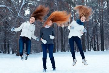 Portrait of three beautiful girls in winter park