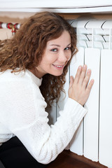 Smiling woman leaning his hand and cheeks to heating radiator
