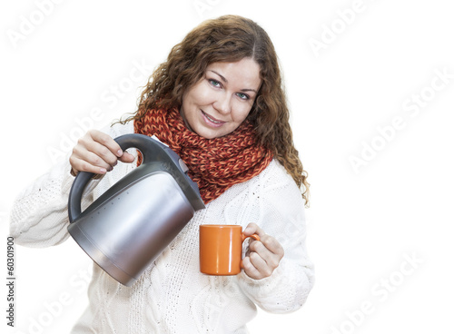 Pretty woman pouring hot water from the kettle into cup