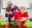 elderly couple cooking with tomatoes