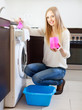 Long-haired woman doing laundry with detergent
