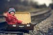 boy sitting in a suitcase near the railway journey