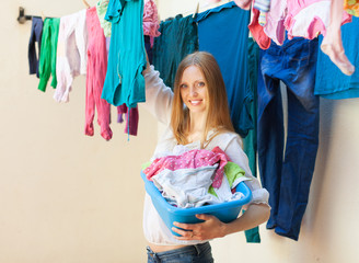 Smiling woman hanging clothes to dry