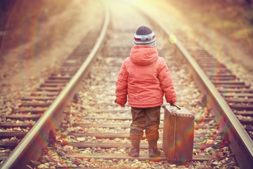little traveler with a suitcase on the railroad