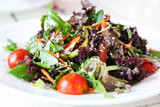 Fresh vegetable salad with arugula on white plate