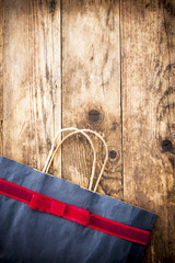 Gift bag with ribbon on the wooden background.