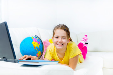 cute little girl on a sofa with a laptop and globe