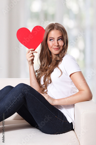 Portrait of a beautiful young woman holding a cardboard heart