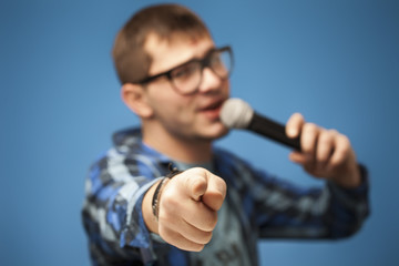 singing using microphone on blue background