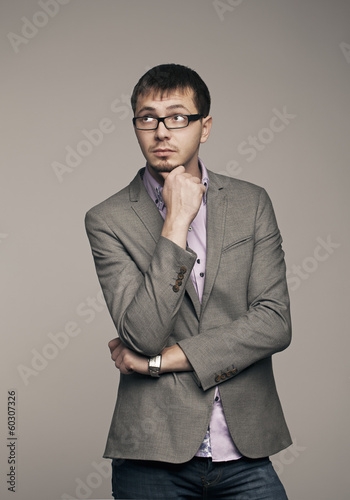 Young man thinking. Studio photo on gray background.