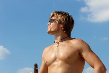 Спортивный парень на фоне голубого неба.