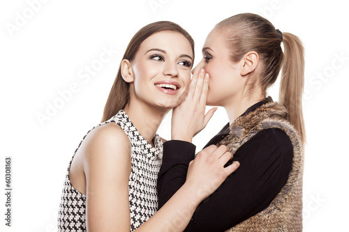 one girl whispers good news to another girl