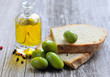 Green olives with pieces of bread and a bottle of oil on wooden