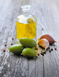 Green olives with bottle of oil on wooden background