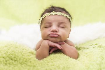 Newbornpose Baby auf grünem Plüsch