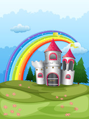 A castle at the hilltop with a rainbow