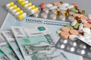 Таблетки и деньги на фоне медицинского полиса