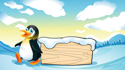 A penguin and an empty wooden template in the snowy area