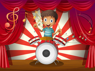 A boy at the center of the stage with a drum