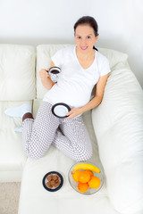 Beautiful pregnant woman drinking coffee on sofa at home