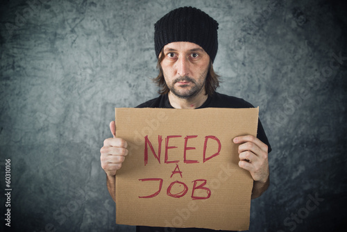 Man holding cardboard paper with Need a Job message